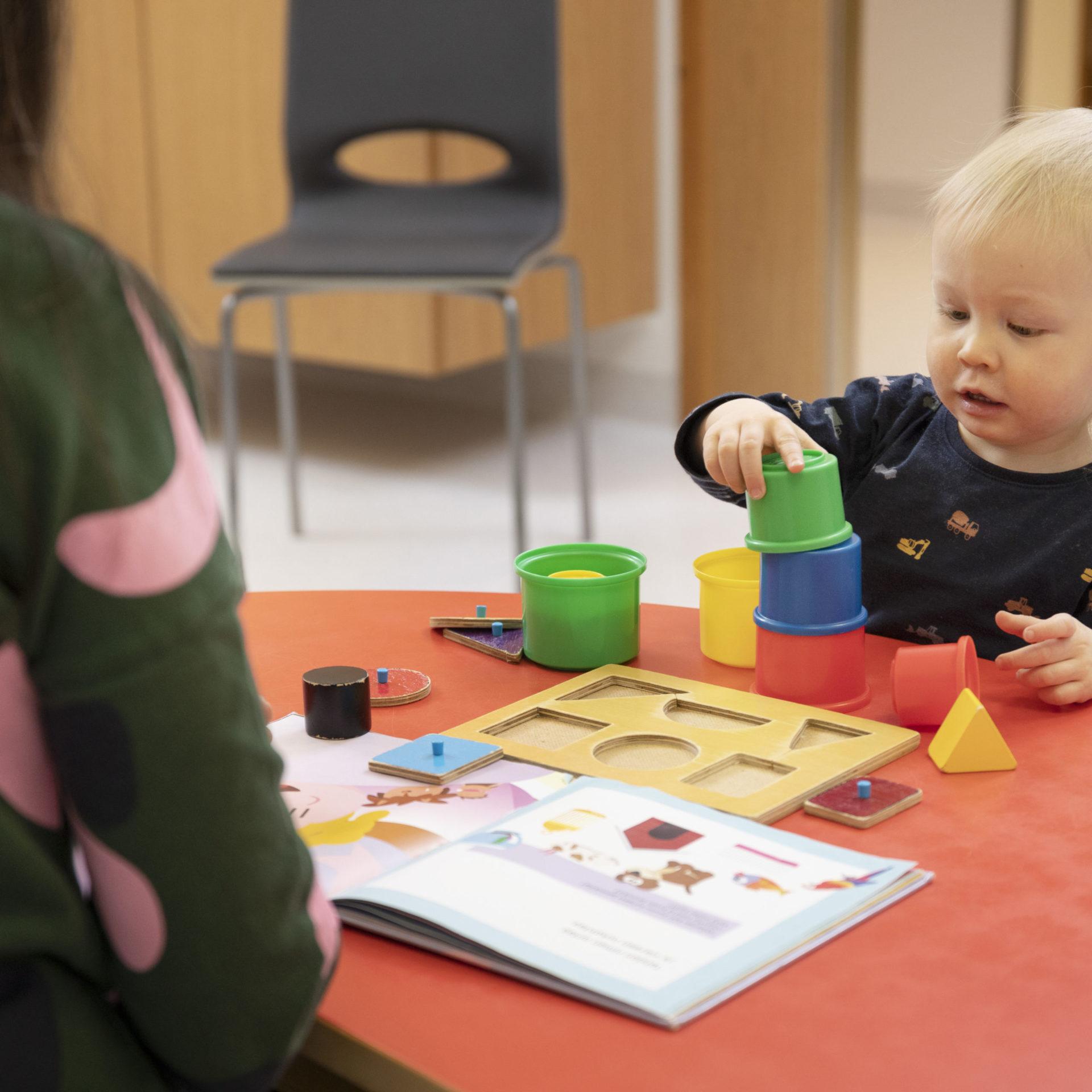 Lapsi tekee neuvolakäyntiin liittyviä tehtäviä neuvolaterveydenhoitajan kanssa.