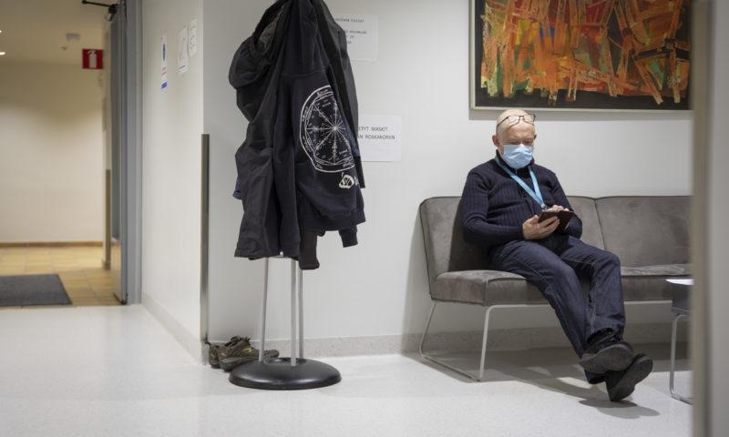 Eläkeläinen istuu ja selaa puhelinta terveyskeskuksen odotustilassa.