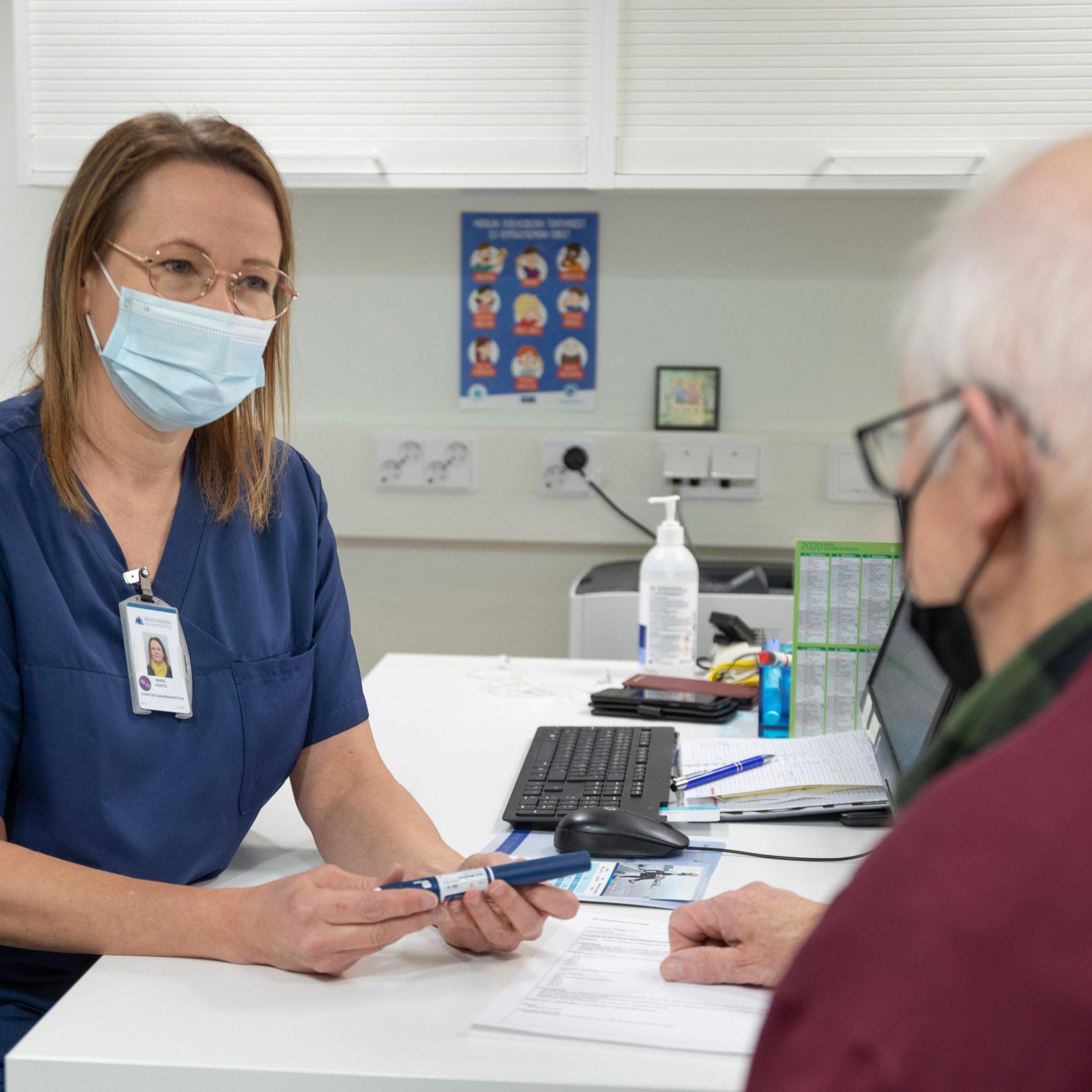 Sairaanhoitaja keskustelee potilaan kanssa.