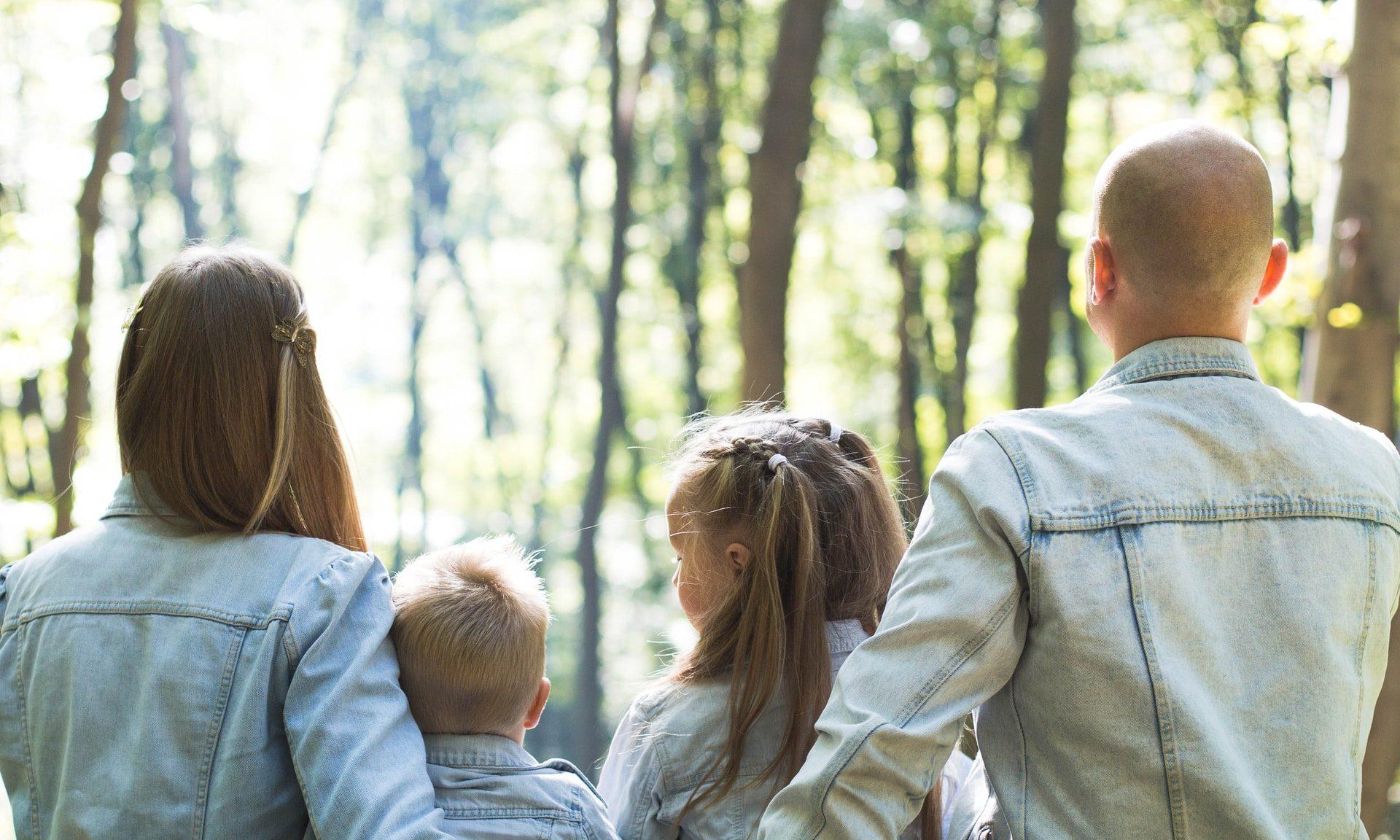 Nelihenkinen perhe nauttii luonnosta metsässä.
