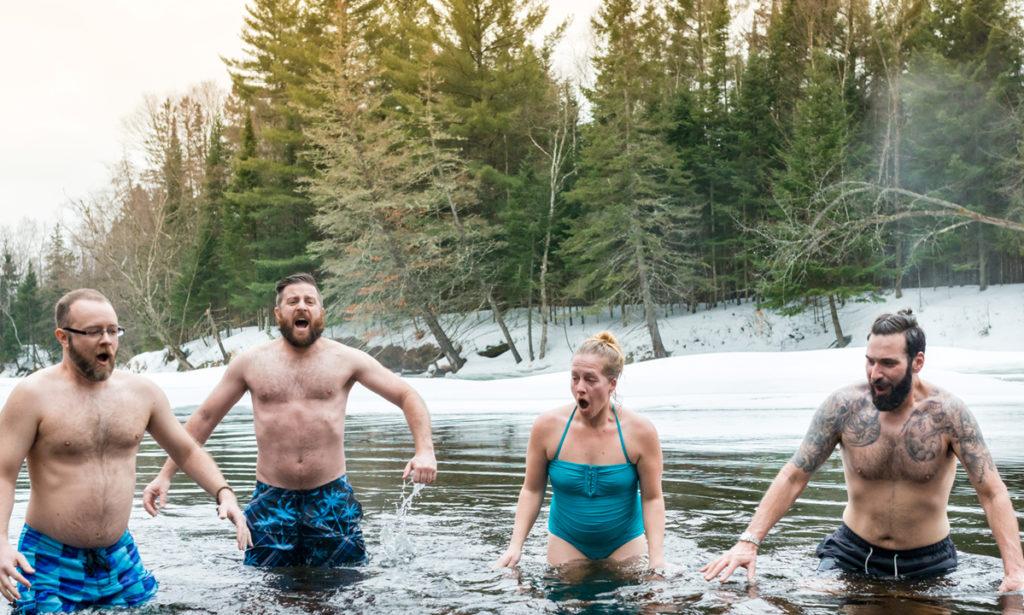 Ryhmä uimareita talvisessa lammessa.