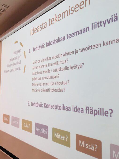 PowerPoint-esitys valkokankaalla, jossa ohjeita työpajaan.